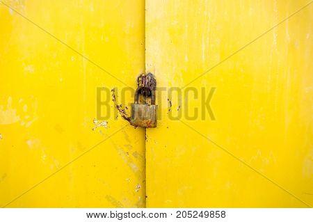 Yellow color rustic metal door with padlock background
