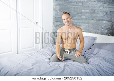 A Young man in bed ear music with cellphone