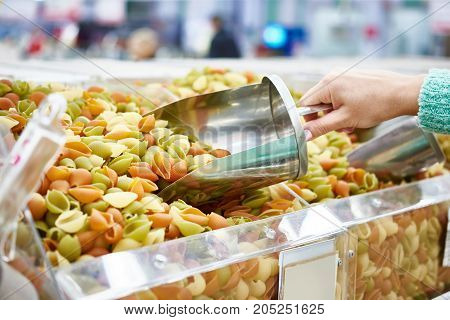 Buyer Picks Up Pasta In Store Using Metal Scoop