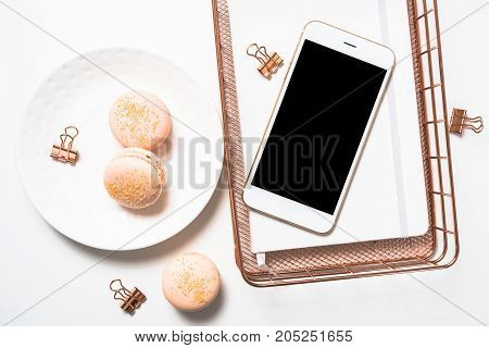 Social media feminine flat lay with orange macaroons, flowers and smartphone mockup on white table background