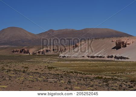 Eroded cliffs along the wide valley of a tributary of the River Lauca high on the Altiplano of northern Chile in Lauca National Park.