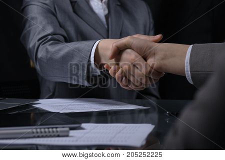 Businesspeople or lawyers shaking hands at meeting. Close-up of human hands at work. Signing contract concept. Low key lighting.