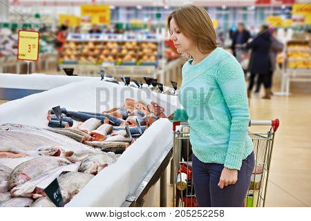 Woman Chooses Fresh Fish In Supermarket