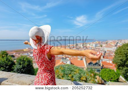 Happy woman with open arms admiring 25 April Bridge, Tagus river and Baixa District from Sao Jorge Castle in Alfama, Lisbon, Portugal. Female tourist enjoys of aerial views. Freedom and travel concept