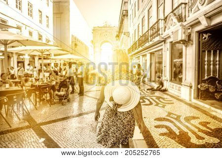 Tourism in Europe. Woman walking on Rua Augusta between cafes and shops in Baixa, downtown of Lisbon, Portugal. Triumphal Arch and King Dom Jose I on defocused background. Sepia color in sunset light.