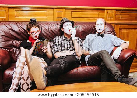 Three Mimes Rest On The Couch Before The Performance