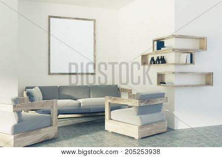 White living room interior with a concrete floor bookshelves two gray and wooden armchairs a sofa and a vertical poster. 3d rendering mock up