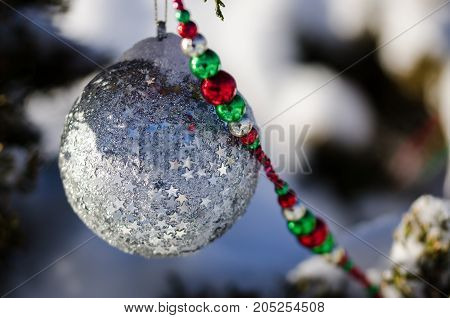 Silver Starred Christmas Ornament Decorating a Snowy Outdoor Tree