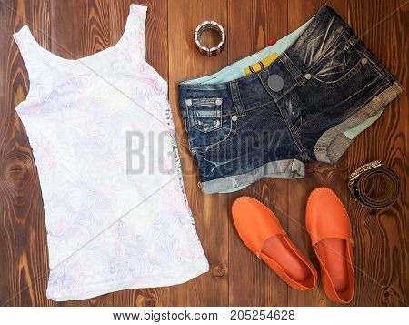 Summer clothes on wooden background. View from above