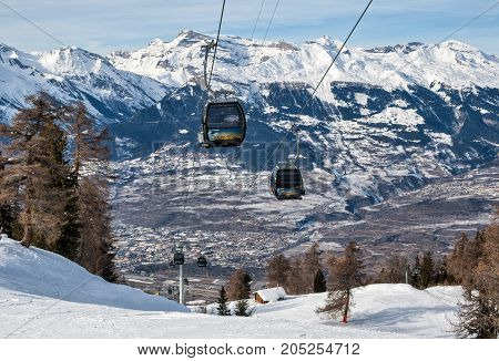 VEYSONNAZ SWITZERLAND - FEBRUARY 04 2010: The cable car to the picturesque background of snow-capped peaks