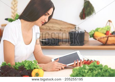 Beautiful Hispanic  woman is making online shopping by tablet computer and credit card. Housewife found new recipe for cooking in a kitchen