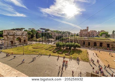 ROME ITALY - MAY 30 2017: View with Temple of Venus and Arch of Constantine from the height of the Colosseum. Evening time. Tourists outside.