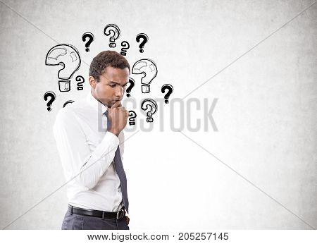 Portrait of a young pensive African American businessman wearing a white shirt and a gray tie. Concrete wall background with many question marks on it Mock up
