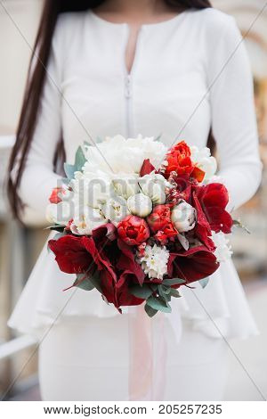 Groom wearing blue jacket holding red and white wedding bouquet close-up