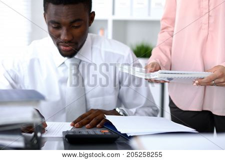African american bookkeeper or financial inspector  making report, calculating or checking balance. Internal Revenue Service checking financial document. Audit concept.