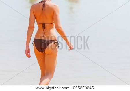 Unknown young and sexy Caucasian girl entering the sea.