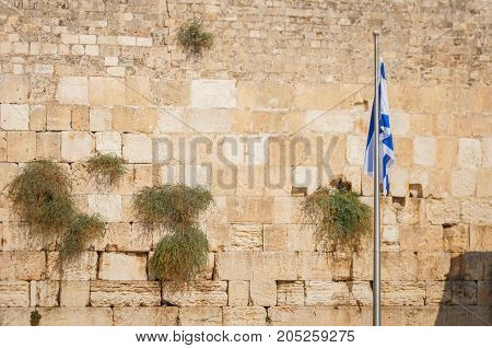 JERUSALEM, ISRAEL. September 15, 2017. A view of the Western Wall with the Flag of Israel. It is a holy place for the Jewish people, a part of the historical Jewish Temple destroyed by the Romans.