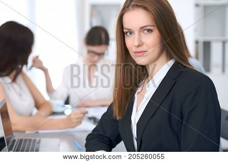 Beautiful business woman smiling at meeting or negitiation.