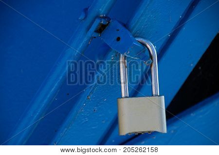 stainless steel secure padlock on blue metal latch