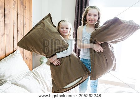 A Portrait kids fighting with pillows in bed