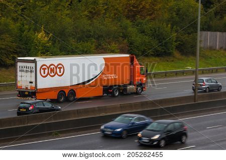 Redbourn UK - September 21 2017: Lorry belonging to TNT Express international courier delivery services company in motion on the British M1 motorway in a rainy day