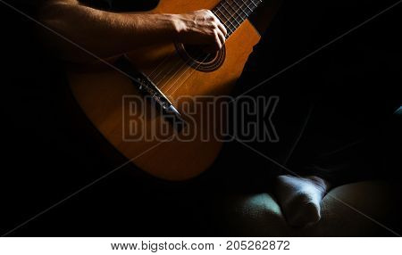 a man plays an acoustic guitar in a room at home a hobby a musician