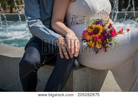 Hands of the groom and the bride with wedding rings and a wedding bouquet