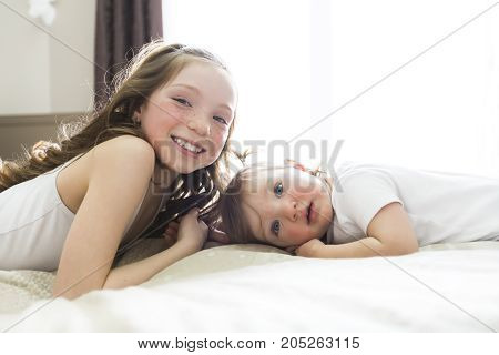 A Little sister Toddler kid on bed having fun