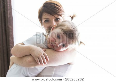 A happy family mother playing with toddler baby