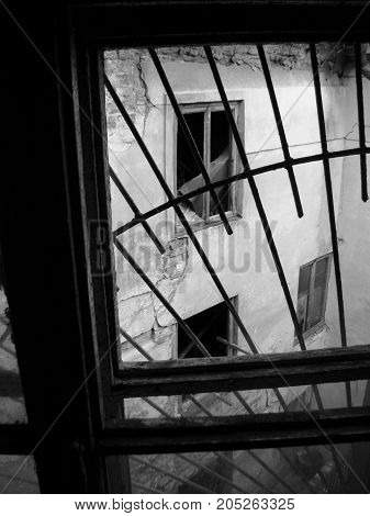 Through a window with an iron grating, emptiness and destruction are visible.