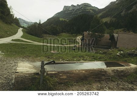 wooden fountain drop in front of hiking trails and alps