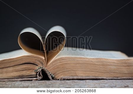 An old book with heart-shaped pages dark background.