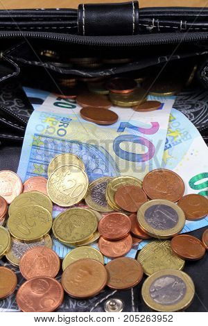 Euro coins and notes take out of a black leather purse