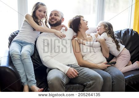 A Family sitting in living room watching tv