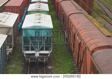 Old freight rail cars are on the track at the railway station