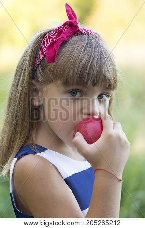 Close up portrait of a beautiful little girl while eating an apple outside. She looks in the camera