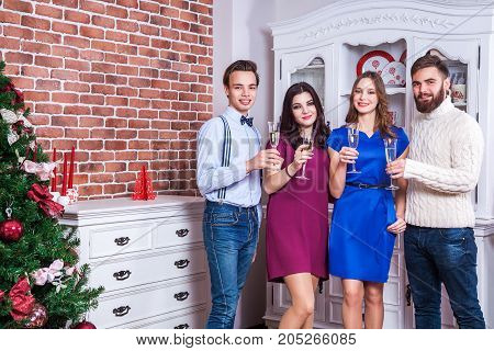 Beautiful Young Adult Friends Toasting With Champagne Near Christmas Tree.