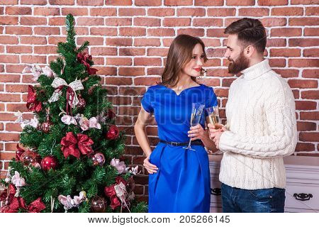 Beautiful Young Couple Is Celebrating Christmas At Home. Look At Each Other Eyes And Smiling.