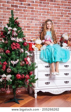 Beautiful Teenage Blonde Sit On A White Nightstand Near Christmas Tree, With Many Toys And Gifts.