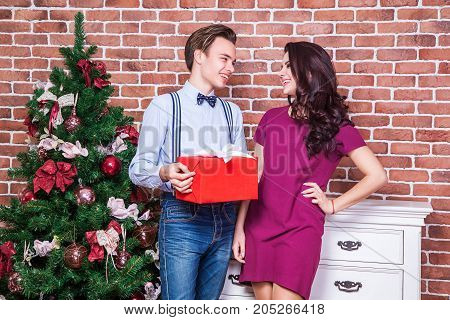 Beautiful Young Couple Is Celebrating Christmas At Home. Boyfriend Present Gift His Girl. Look At Ea