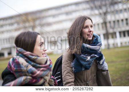 Two beautiful teenage students together outside in the school