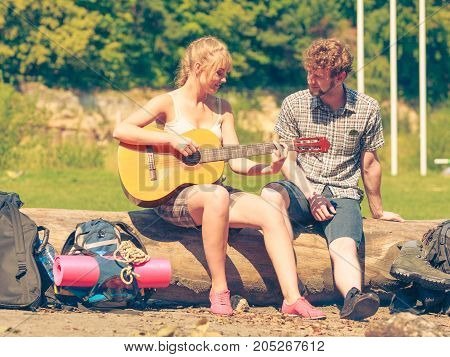 Adventure tourism enjoying summer time together - young couple tourists having fun playing guitar in camping