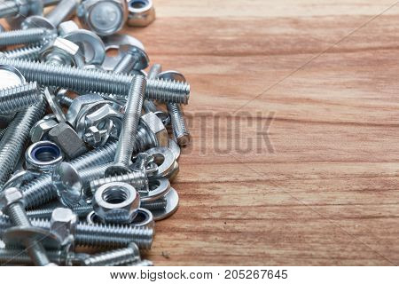 Pile of differents screws and bolts on wooden table. Background