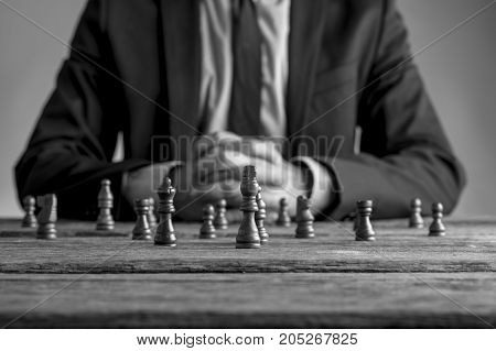 Businessman Wearing Suit Sitting In Front Of Dark Chess Pieces