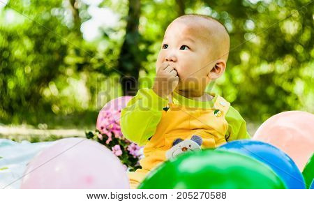 baby is playing with balloons in the park