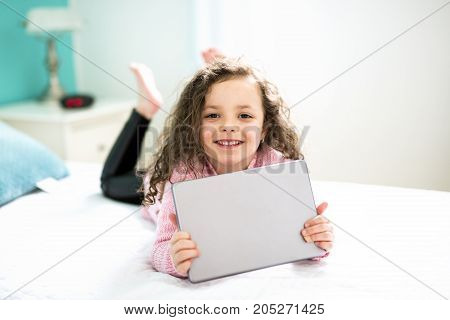 When Technologies become easier. Cute little girl holding digital tablet and smiling while lying in bed.