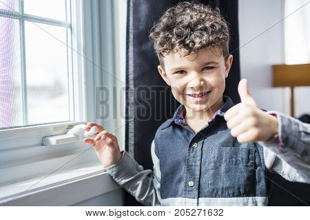 A happy boy close to a window at home