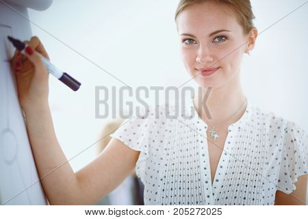 Businesswoman writing on flipchart while giving presentation to colleagues in office . Businesswoman.