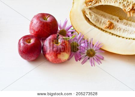 three red apples and pieces of melon on the plate and cut the next melon  flowers Aster on a white background
