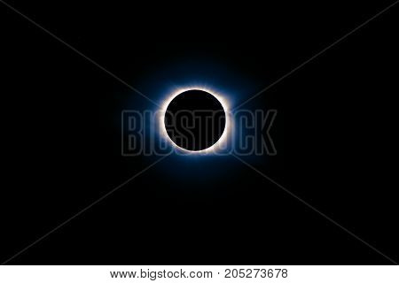 solar eclipse during totality with blue and pink hues